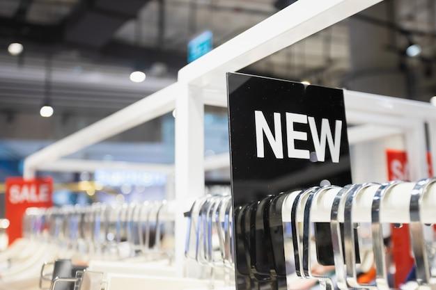 Neues label am kleiderständer im frauenkleidungsshop.