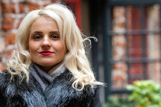 Neues, lächelndes, blondes frauenporträt auf dem defokussierten backsteingebäude