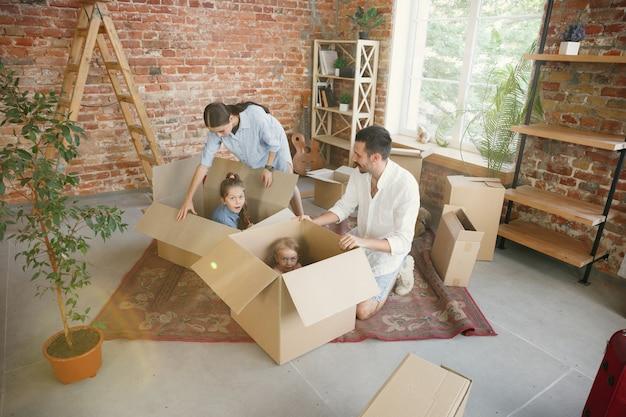 Neues leben. erwachsene familie zog in ein neues haus oder eine neue wohnung. ehepartner und kinder sehen glücklich und selbstbewusst aus. bewegung, beziehungen, neues lebenskonzept. kisten mit ihren sachen auspacken, zusammen spielen.
