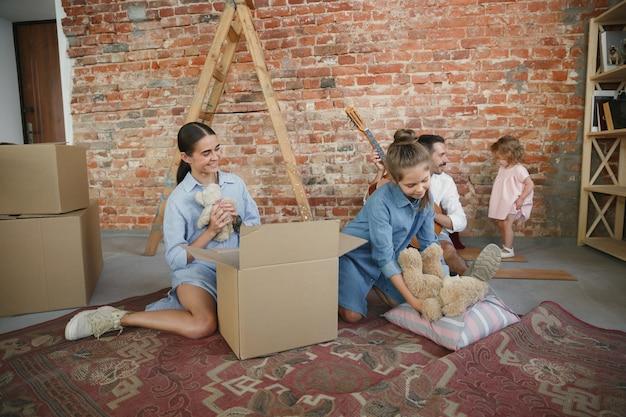 Neues leben. erwachsene familie zog in ein neues haus oder eine neue wohnung. ehepartner und kinder sehen glücklich und selbstbewusst aus