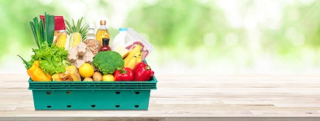Neues lebensmittel und lebensmittelgeschäfte im behälterkasten auf hölzernem tischplattenfahnenhintergrund