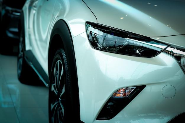 Neues luxuriöses weißes auto im modernen ausstellungsraum geparkt. autohausbüro. elektro- oder hybridautotechnik und geschäftskonzept. automobilindustrie.