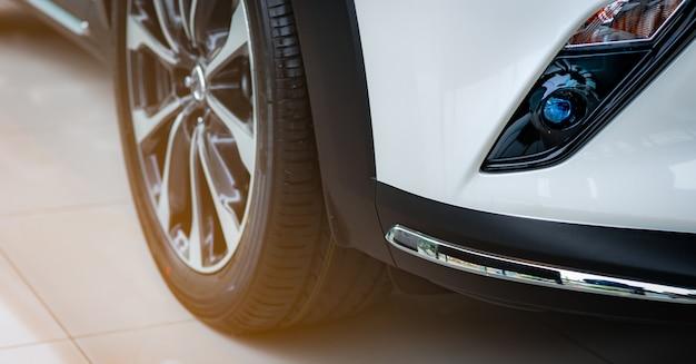 Neues luxuriöses weißes auto im modernen ausstellungsraum zum verkauf geparkt. autohausbüro. autohaus. elektro- oder hybridautotechnik. automobilindustrie.