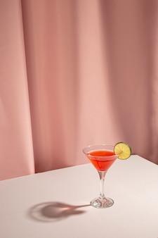 Neues margaritacocktailgetränk mit zitronenscheibe auf tabelle gegen rosa vorhang