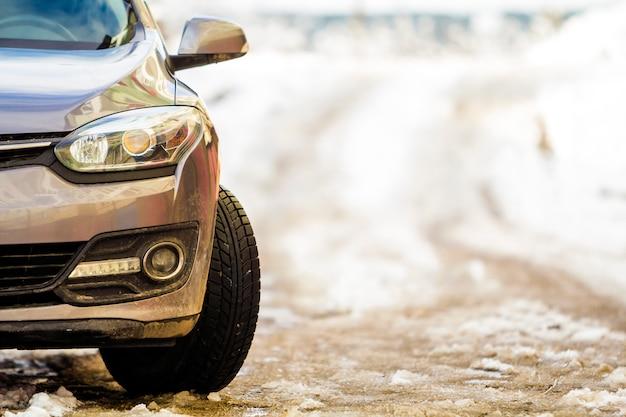 Neues modernes graues auto, das im winter auf einer straße geparkt wird