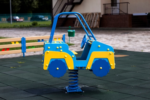 Neues modernes plastisches helles buntes blaues und gelbes großes spielzeugauto auf frühling auf kinderspielplatz mit weichem gummiboden am hellen sonnigen sommertag. perfekter ort für aktivitäten für kinder im freien.