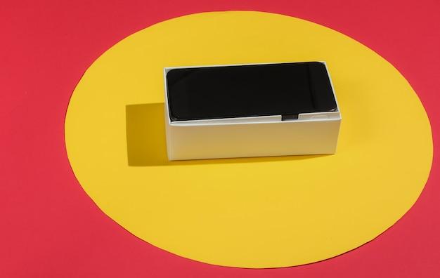 Neues modernes smartphone in box auf rot mit gelbem kreis in der mitte