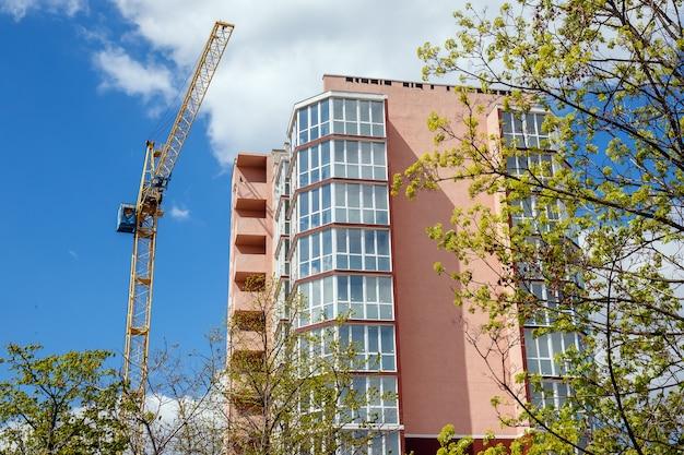 Neues modernes wohnhaus und grüne bäume auf einem hintergrund des blauen bewölkten himmels am sonnigen tag.