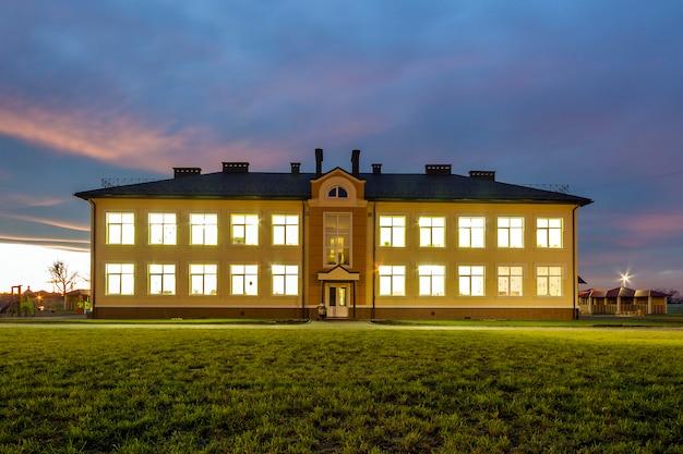 Neues modernes zweistöckiges kindergartenvorschulgebäude mit hell beleuchteten fenstern auf grünem grasartigem rasen und glättendem kopienraumhintergrund des blauen himmels. architektur- und entwicklungskonzept.