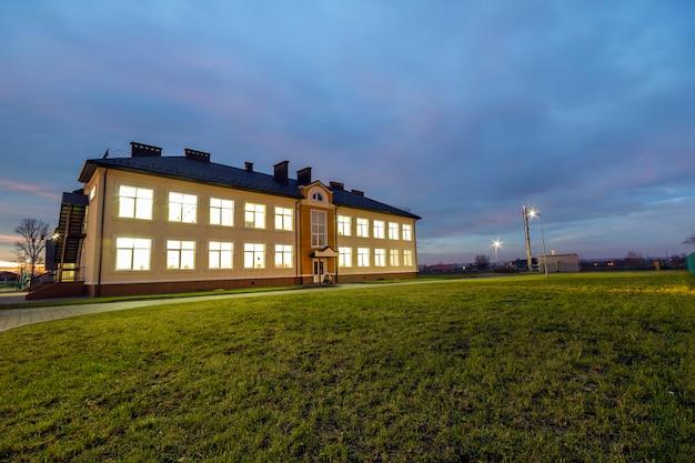 Neues modernes zweistöckiges kindergartenvorschulgebäude mit hell beleuchteten fenstern auf grünem grasartigem rasen.