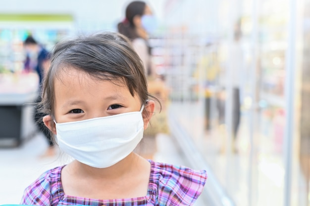Neues normales kleines mädchen hat stoffmaske, die sich vor coronavirus schützt