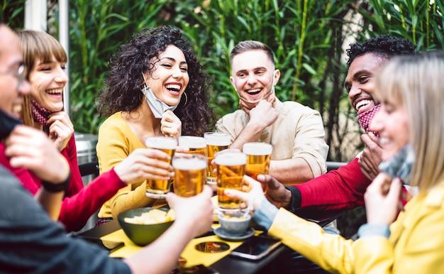 Neues normales lebensstilkonzept mit freunden, die spaß zusammen draußen im bargarten haben