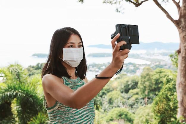 Neues normales reisekonzept, glückliche reisende asiatische frau mit maske und kamerabesichtigung im kata-strand-aussichtspunkt, phuket, thailand
