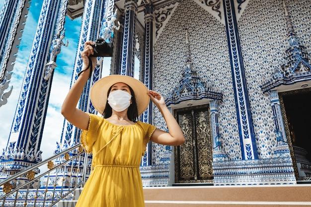 Neues normales reisekonzept, glückliche reisende asiatische frau mit maske und kamerabesichtigung in wat pak nam khaem
