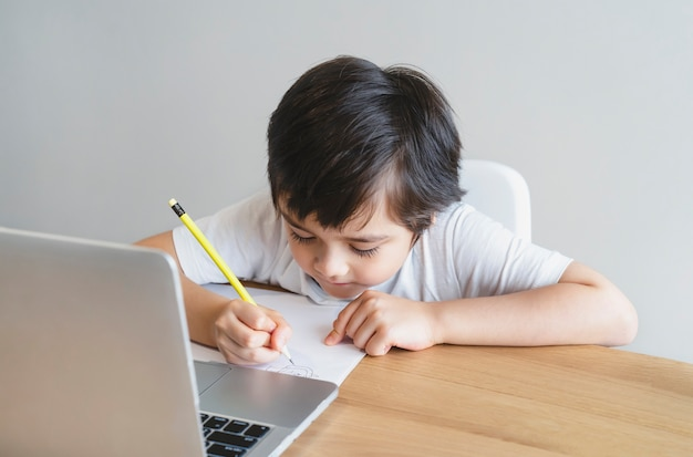 Neues normales schulkind, das computer für seine hausaufgaben benutzt. e-learning-online-bildungskonzept