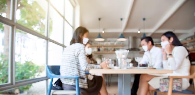Neues normales verhalten in der mittagspause mit freunden, gesichtsmasken im restaurant tragend
