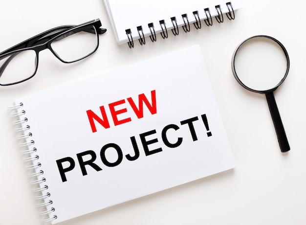 Neues projekt ist in einem weißen notizbuch auf einer hellen oberfläche in der nähe des notizbuchs, einer schwarz gerahmten brille und einer lupe geschrieben