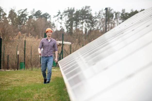 Neues projekt. junger erwachsener mann in schutzhelm mit zeichnung in der hand, der in der nähe von sonnenkollektoren auf dem land geht