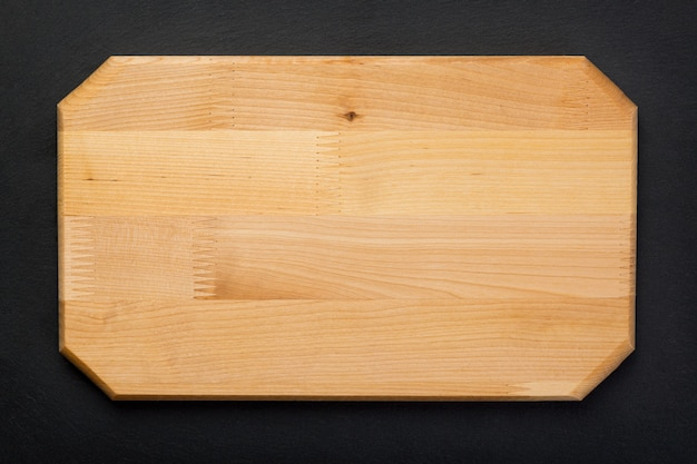 Neues rechteckiges holzschneidebrett auf schwarzer steinschieferplatte. modell für lebensmittelprojekt. ansicht von oben.
