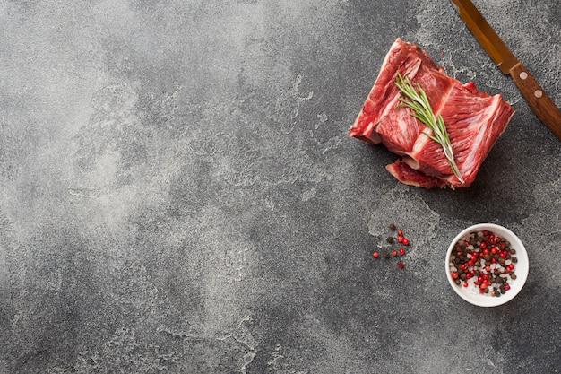 Neues rohes stück rindfleischrippe mit fleisch auf einer dunklen betondecke