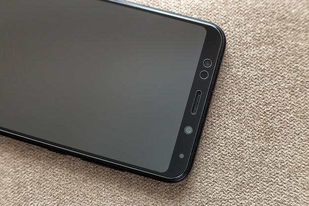 Neues schwarzes modernes handy lokalisiert auf hellem stoffkopierraumhintergrund. modernes technologie-, kommunikations- und gadget-designkonzept.