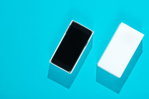 Neues smartphone in offener box auf blauem papiertisch. draufsicht, minimalismus