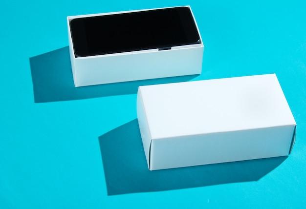 Neues smartphone in offener box auf blauem papiertisch. seitenansicht, minimalismus