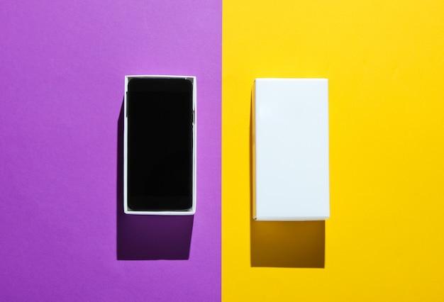 Neues smartphone in offener box auf farbigem papiertisch. draufsicht, minimalismus