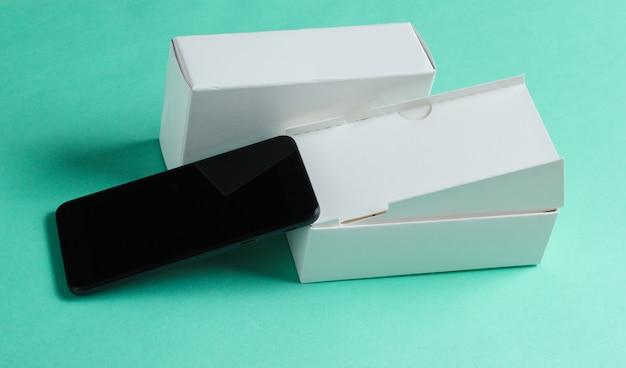 Neues smartphone mit box auf blauer oberfläche. konzept, unboxing