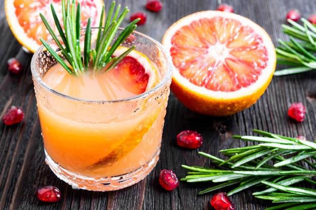 Neues sommergetränk mit blutorange und rosmarin in einem glas auf dunklem hölzernem hintergrund.
