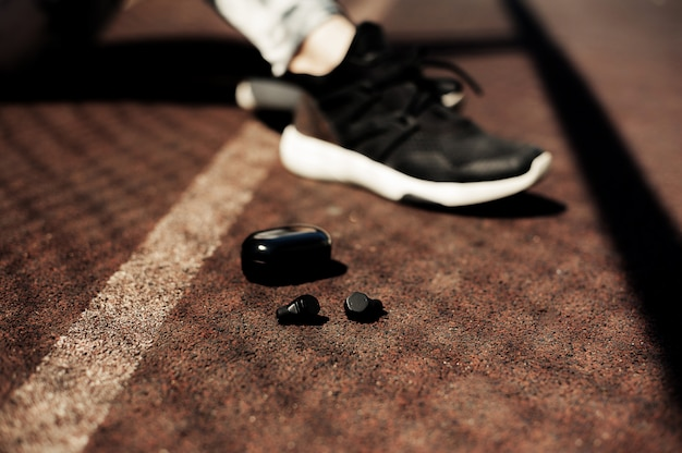 Neues, sportlich tragbares zubehör für läufer: drahtlose kopfhörer, laufschuhe. ohrhörer, er
