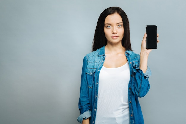 Neues telefon. aufmerksame frau, die auf kamera mit telefon in der linken hand aufwirft und über grauem hintergrund steht, während sie nach vorne schaut