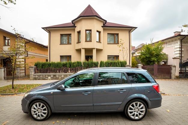 Neues teures graues auto geparkt auf gepflastertem parkplatz vor großem zweistöckigem häuschen.