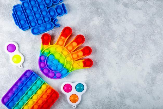 Neues trendiges silikonspielzeug antistress pop it und einfaches grübchen auf hellgrauem hintergrund