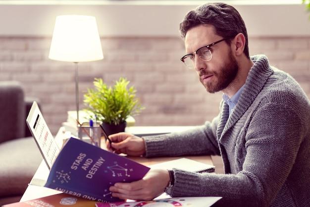 Neues wissen kluger netter mann, der während seiner arbeit ein buch über astrologie liest