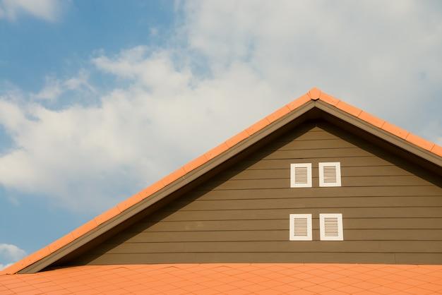 Neues ziegelhaus mit modularem schornstein, steinbeschichtetem metalldachziegel, kunststofffenstern und regenrinne