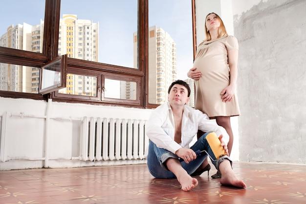 Neues zuhause. ehemann und schwangere frau im neuen haus.
