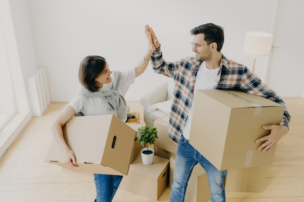 Neues zuhause. glückliche frau und mann feiern umzug in neue wohnung