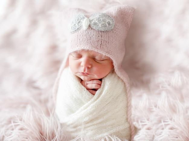 Neugeboren im beaniehut auf einem zotteligen teppich