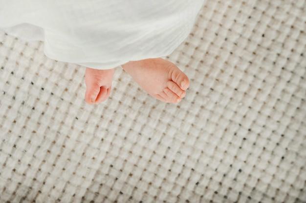 Neugeborene babyfüße in einer weißen windelnahaufnahme. babyfüße in musselinwindel und kopierraum.