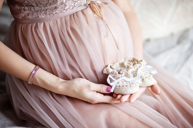 Neugeborene babyschuhe in den händen der mutter