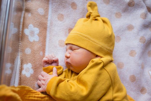 Neugeborene erste lebenstage im kreißsaal. säugling schläft im krankenhaus nach der geburt.