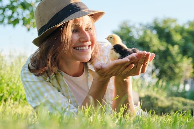 Neugeborene hühner in der hand der bäuerin, rustikaler stil, landwirtschaft