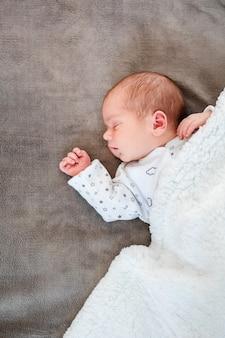 Neugeborene schlafen in den ersten lebenstagen. nettes kleines neugeborenes kind, das friedlich schläft.
