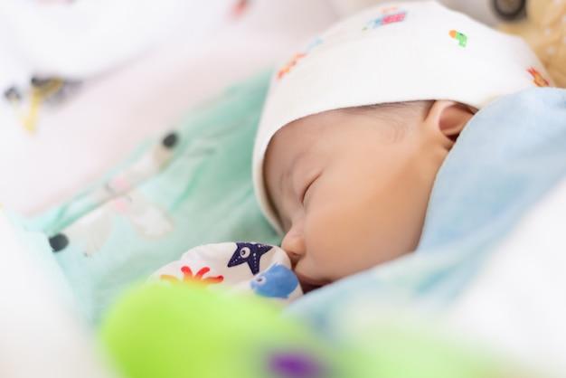 Neugeborene und mothercare-konzept. säuglingsbaby-asiatisches jungenschlafen