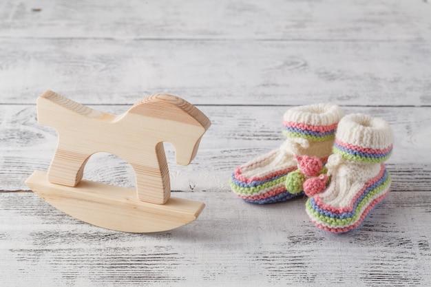 Neugeborenen-ankündigungsvorlage. handgemachte gestrickte stiefeletten mit spielzeug