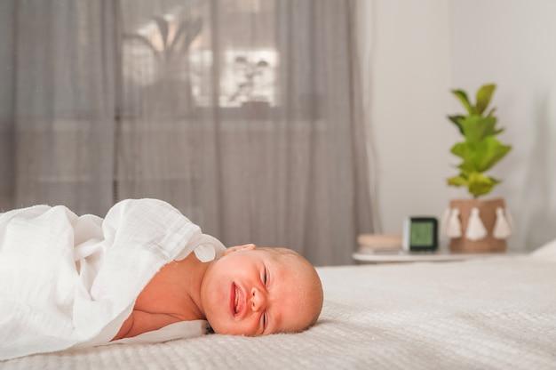Neugeborenes auf dem bett. weinen, baby schreien hautnah und raum kopieren. baby lächeln und kolik bei neugeborenen.
