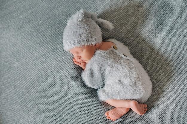 Neugeborenes baby, 9 tage alt, schlafend und eingewickelt in eine graue decke in einem grauen hintergrund.