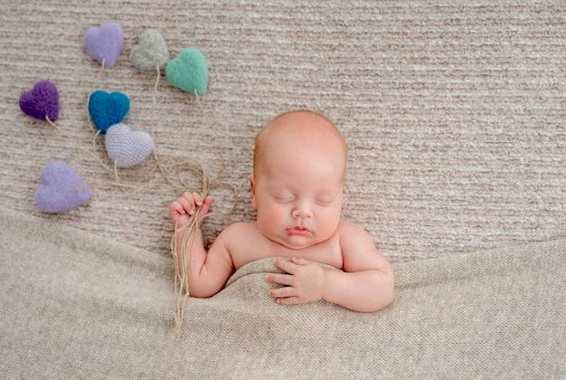 Neugeborenes baby auf beigem hintergrund, das unter decke schläft und gestricktes spielzeug hält