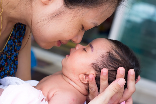 Neugeborenes baby auf den händen der mutter. mutter, die kopf ihres neugeborenen babys in den händen hält.